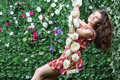 Happy woman swings on swing overgrown with flowers. Next to green hedge with flowers Stock Images