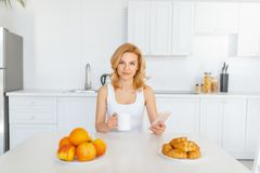 Happy woman at the table with fruits and baking royalty free stock images