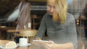 Happy woman with tablet computer in cafe stock video