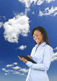 Happy woman with tablet computer and clouds stock image