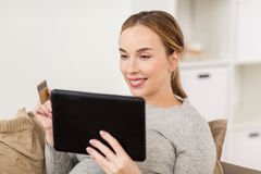Happy woman with tablet pc and credit card Royalty Free Stock Image