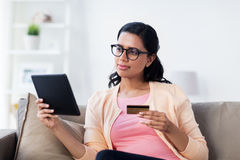 Happy woman with tablet pc and credit card at home Royalty Free Stock Images