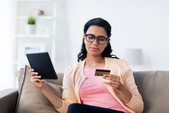 Happy woman with tablet pc and credit card at home Stock Image