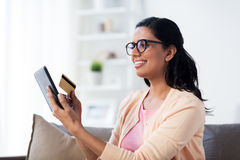 Happy woman with tablet pc and credit card at home Stock Photos