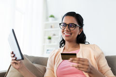 Happy woman with tablet pc and credit card at home Royalty Free Stock Photography