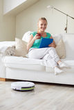 Happy woman with tablet pc drinking tea at home Stock Photo