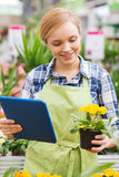 Happy woman with tablet pc in greenhouse Stock Image