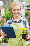 Happy woman with tablet pc in greenhouse Royalty Free Stock Photo