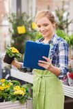 Happy woman with tablet pc in greenhouse Stock Photography