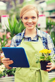 Happy woman with tablet pc in greenhouse Royalty Free Stock Images