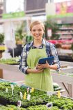 Happy woman with tablet pc in greenhouse Stock Images
