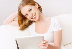 Happy woman with tablet pc at home Royalty Free Stock Images