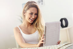 Happy woman with tablet on sofa royalty free stock images