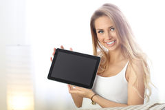 Happy woman with tablet on sofa stock photos