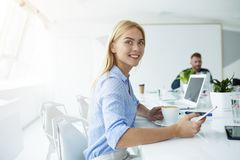 Happy woman takes a coffee break during her work. Happy women in office takes a coffee break during her work stock photography