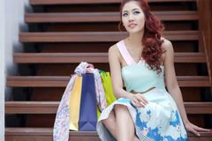 Happy woman taking a break with shopping bags while sitting on t Royalty Free Stock Photos