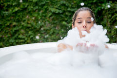 Happy woman taking a bubble bath Stock Photography