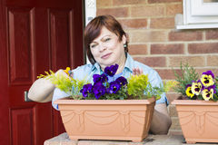 Happy woman taking care of flowers outdoors Royalty Free Stock Photography