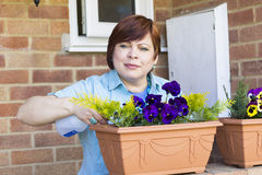 Happy woman taking care of flowers outdoors Stock Photos
