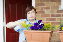 Happy woman taking care of flowers outdoors Stock Image