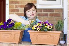 Happy woman taking care of flowers outdoors Royalty Free Stock Images