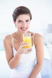 Happy woman taking drinking glass of orange juice Stock Photo