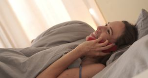 Happy woman taking on mobile phone in bed. Happy woman talking on mobile phone before going to sleep in bed stock video