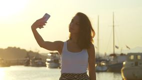 Happy woman taking mobile photo in evening port. Travel girl posing for selfie stock footage