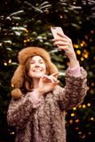 Happy woman taking photos on the Christmas decorated street royalty free stock photography