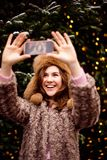 Young woman in winter clothes making selfie using a smart phone and smiling royalty free stock photography