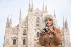 Happy woman taking photos near of Duomo while sightseeing Milan Stock Photos