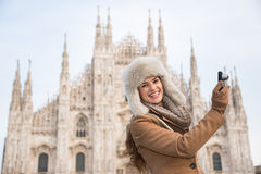 Happy woman taking photos near of Duomo while sightseeing Milan Royalty Free Stock Photography