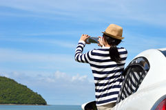 Happy woman taking photos to the sea. With smartphone camera on car Royalty Free Stock Image