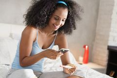 Happy Woman Taking Picture of Pregnancy Test Kit. Happy young latino woman taking photo of pregnancy test kit with mobile phone and posting picture on social royalty free stock photography