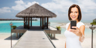 Happy woman taking picture by smartphone on beach Royalty Free Stock Image