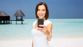 Happy woman taking picture by smartphone on beach royalty free stock photo