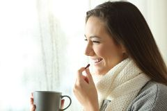 Happy woman taking a pill in a rainy day of winter Stock Photography