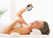 Happy woman taking self photo while laying on massage table Stock Images