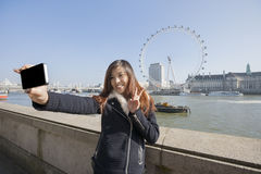 Happy woman taking self portrait through cell phone against London Eye at London, England, UK Royalty Free Stock Photography