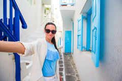 Happy woman taking selfie on deserted streets of greek village. Young beautiful woman on vacation exploring european. Caucasian tourist walking along the Stock Images