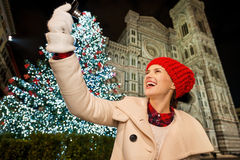 Happy woman taking selfie near Christmas tree in Florence, Italy. Happy young woman in white coat taking selfie in front of Christmas tree near Duomo in the royalty free stock image