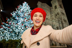 Happy woman taking selfie near Christmas tree in Florence, Italy. Happy young woman in white coat taking selfie in front of Christmas tree near Duomo in the royalty free stock images