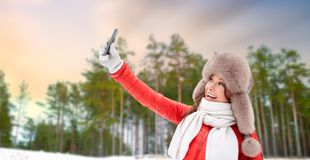 Happy woman taking selfie over winter forest royalty free stock image