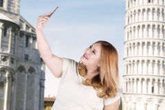 Happy woman taking selfie photo at pizza tower. Portrait of happy woman taking selfie photo by using smartphone in front of pizza tower Royalty Free Stock Photography