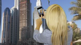 Happy woman taking selfie photo on smart phone opposite business skyscrapers stock footage