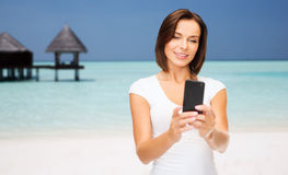 Happy woman taking selfie by smartphone over beach Royalty Free Stock Images