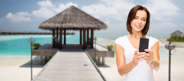 Happy woman taking selfie by smartphone over beach Stock Photo