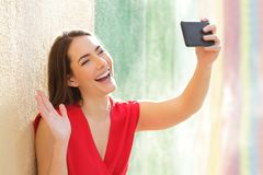 Happy woman taking selfies in a colorful street stock photography