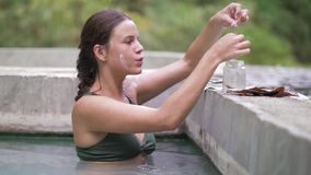 Happy woman taking thermal bath and collecting healing mud for face mask. Young woman enjoying thermal spring in natural.  stock video