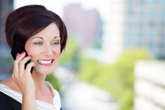Happy woman talking on a cell phone relaxed on a balcony Royalty Free Stock Image